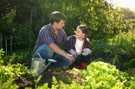 horticulture: Young smiling father teaching daughter horticulture at garden Stock Photo