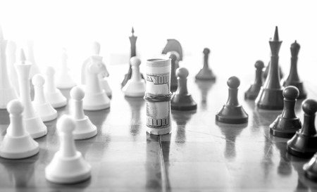 Black and white conceptual photo of wrapped money playing in chess as chess piece