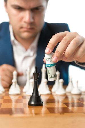 financial official: Conceptual shot of money power. Man making chess move with dollar banknotes Stock Photo