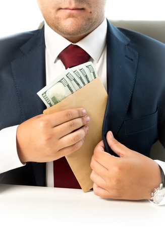 venality: Closeup photo of businessman hiding envelope with money in pocket at jacket Stock Photo