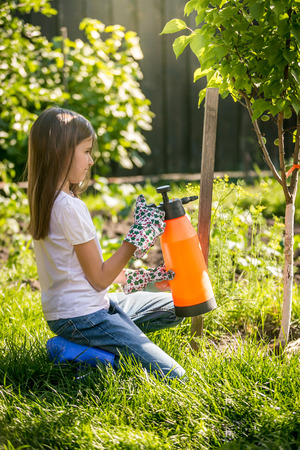 Young brunette girl working in garden with fertilizing spray