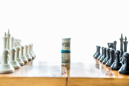 Isolated photo of twisted money on board between rows of chess pieces Stock Photo