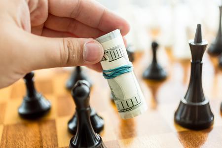 Closeup conceptual photo of man making move at chess game with dollar bills Stock Photo