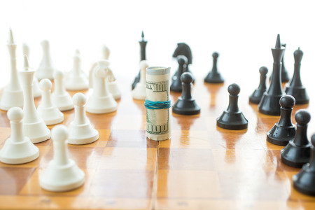 Conceptual shot of twisted money on wooden chessboard photo