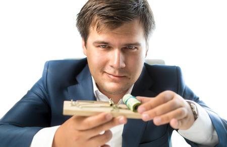위험한 투자를 제공하는 은행의 개념적 사진입니다. 쥐덫 돈을 들고 남자