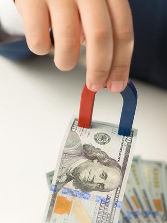 magnetismo: Primer tirado de la mano masculina que sostiene imán y tirando el dinero de pila Foto de archivo