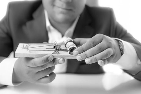 financial official: Black and white closeup photo of businessman holding mousetrap with money as bait Stock Photo