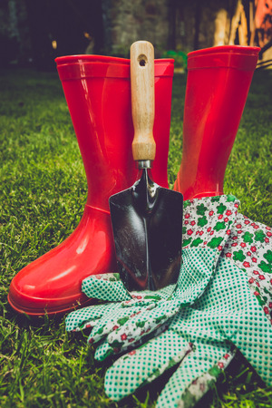 garden tool: Closeup toned filter of garden tools and red boots on meadow
