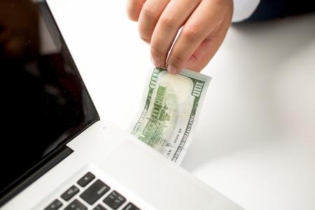 디지털 돈 전송의 개념적 사진입니다. 달러 지폐를 컴퓨터에 삽입하는 사람 스톡 콘텐츠