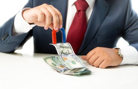 magnetismo: Foto conceptual del hombre de negocios tirando el dinero de pila en la mesa con el imán