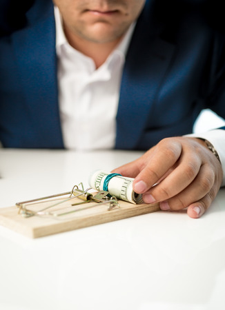 debt trap: Closeup photo of businessman taking money lure from the mousetrap