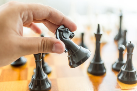 chess move: Closeup photo of male hand holding black horse chess piece