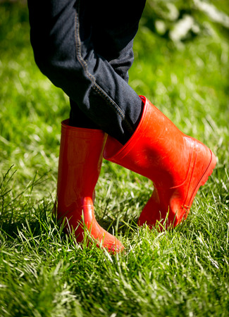 gum boots: Closeup photo of girl in red rubber boots posing on fresh green grass at sunny day