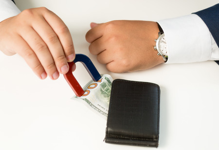 avidity: Closeup shot of man in suit pulling money out wallet with magnet