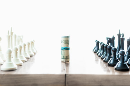 Conceptual shot of chess pieces fighting for twisted dollar bills photo