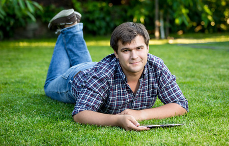 ereader: Young smiling man lying with tablet on lawn at park