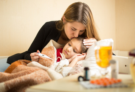 Portret van de jonge zorgzame moeder die zieke dochter in het hoofd