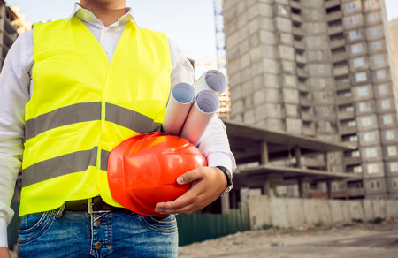 Closeup toned photo of foreman holding helmet and blueprints against building site