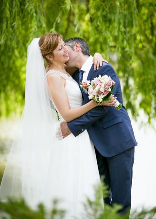 passionately: Portrait of handsome groom passionately kissing bride under tree