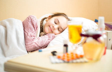 sore: Portrait of sick girl in woolen sweater lying in bed