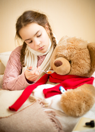 sick teddy bear: Portrait of little girl giving pills to sick teddy bear