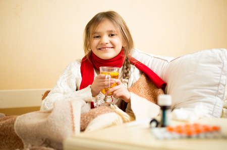 nightdress: Portrait of cute smiling girl sitting in bed and drinking hot tea