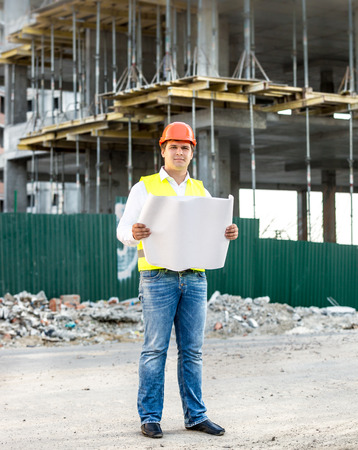 taskmaster: Young architect at work reading blueprints on building site