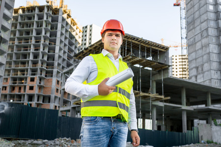 architect: Portrait of architect in red hardhat posing on building site