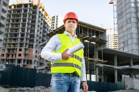 Ritratto di architetto in casco rosso che propone sul cantiere