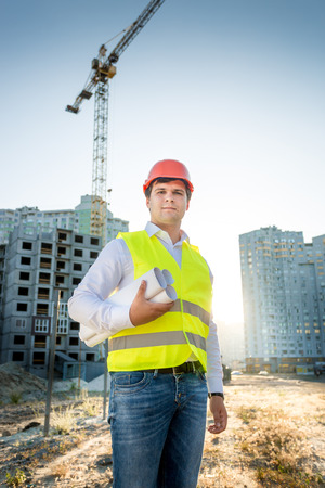 buildingsite: Portrait of young engineer in hardhat and yellow jacket posing with blueprints