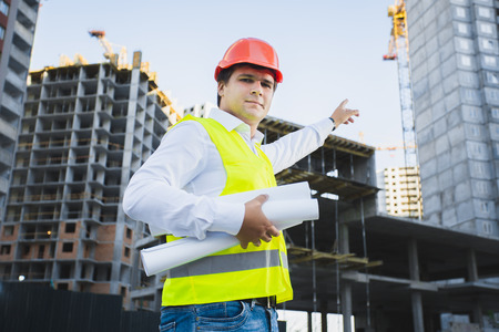 construction project: Closeup portrait of architect in hardhat showing building under construction Stock Photo