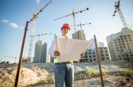 Construction engineer in hardhat inspecting blueprints on building site Foto de archivo