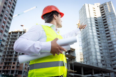 Closeup portrait of foreman with blueprints pointing hand at high building Foto de archivo