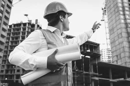 Black and white closeup photo of engineer with blueprints checking building site construction