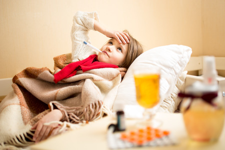 high temperature: Little sick girl with high temperature resting in bed Stock Photo