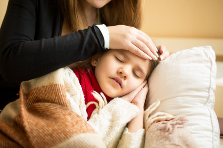 parent child: Closeup photo of caring mother holding head on sick daughter forehead Stock Photo