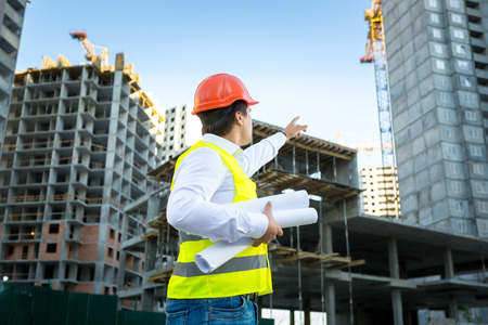 Site manager in hardhat pointing at crane on building site