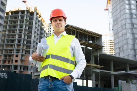 Portrait of site manager posing with blueprints against unfinished building Foto de archivo