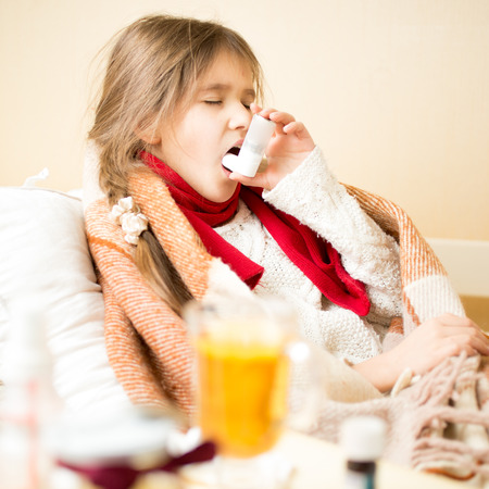 grippe: Portrait of sick girl with respiratory illness lying in bed and using inhaler Stock Photo