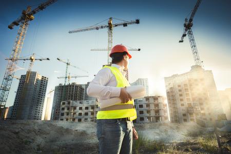 construccion: Hombre en casco y chaqueta verde posando en solar al atardecer