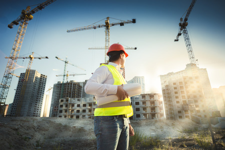 site: Man in hardhat and green jacket posing on building site at sunset