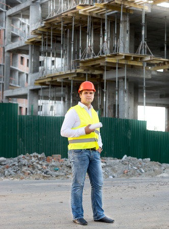 foreman: Foreman in jacket and helmet posing against building in scaffolding