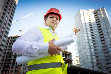 Closeup portrait of foreman in helmet showing building site under construction