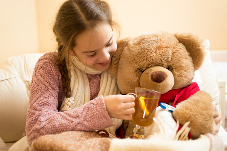 sick teddy bear: Closeup photo of little sick girl giving hot tea to teddy bear
