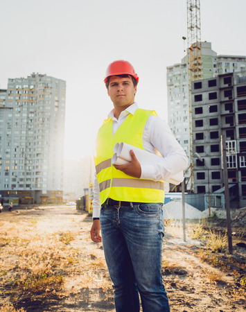 buildingsite: Toned portrait of engineer posing against building site at sunset Stock Photo