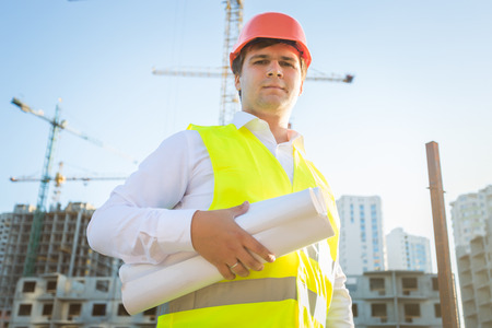 taskmaster: Closeup portrait of construction manager posing with blueprints
