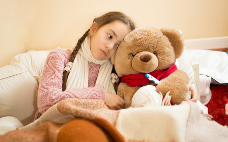 sick teddy bear: Portrait of sick girl resting in bed with brown teddy bear