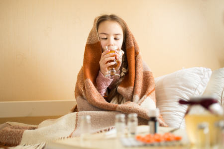 sick: Portrait of cute sick girl covered in blanket drinking hot tea
