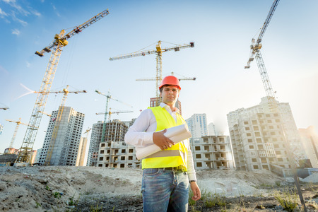 site manager: Portrait of construction inspector posing with blueprints on building site Stock Photo