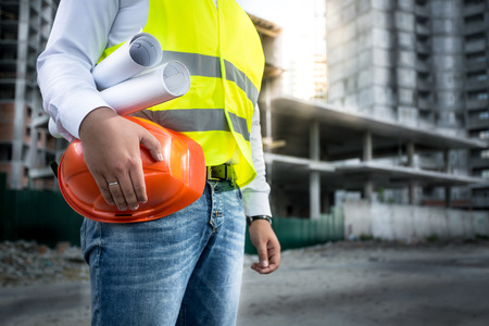 Closeup photo of engineer with hardhat and blueprints posing on building site Archivio Fotografico